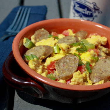 a bowl of scrambled eggs, peppers and sausage