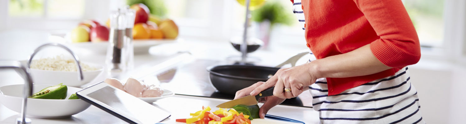 Torso of a woman cutting a pepper while following a recipe